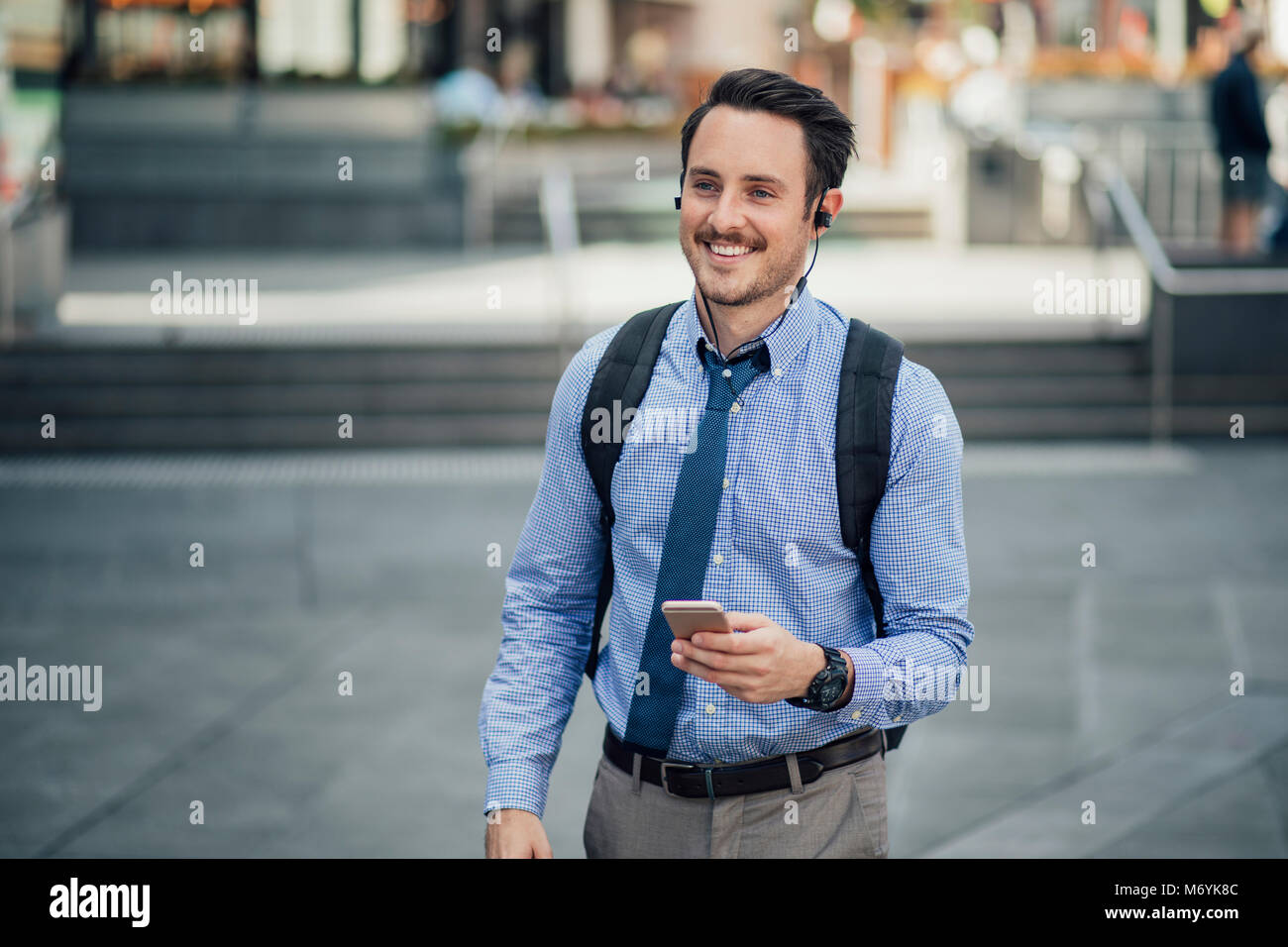 Happy millennial businessman is commuting in Melbourne, Victoria with a smartphone, listening to music through his - Stock Image