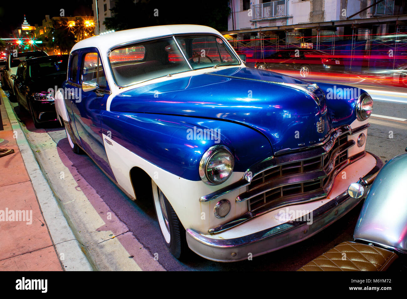 Blue white classic car parked on road in Miami at night Stock Photo ...
