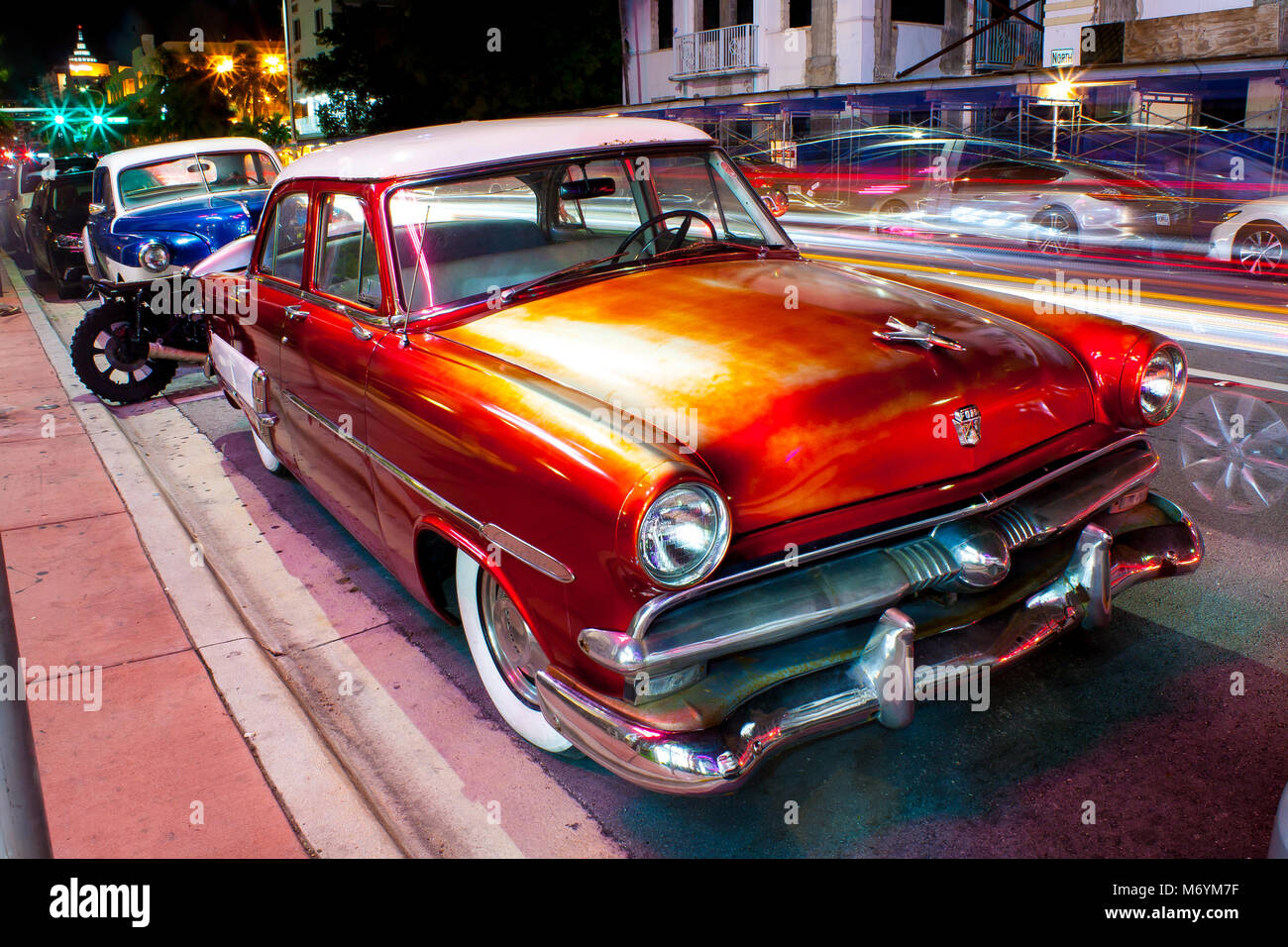 Orange classic car Ford parked on road in Miami at night Stock Photo ...