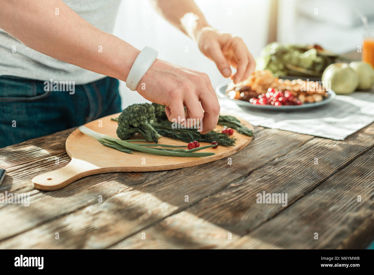 Responsible creative man standing and cooking. - Stock Image