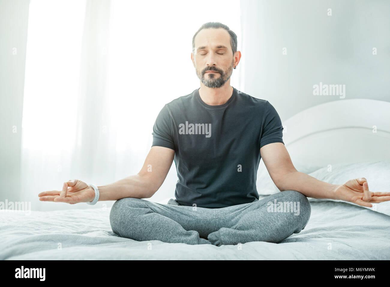 Handsome unshaken man sitting and meditating. - Stock Image