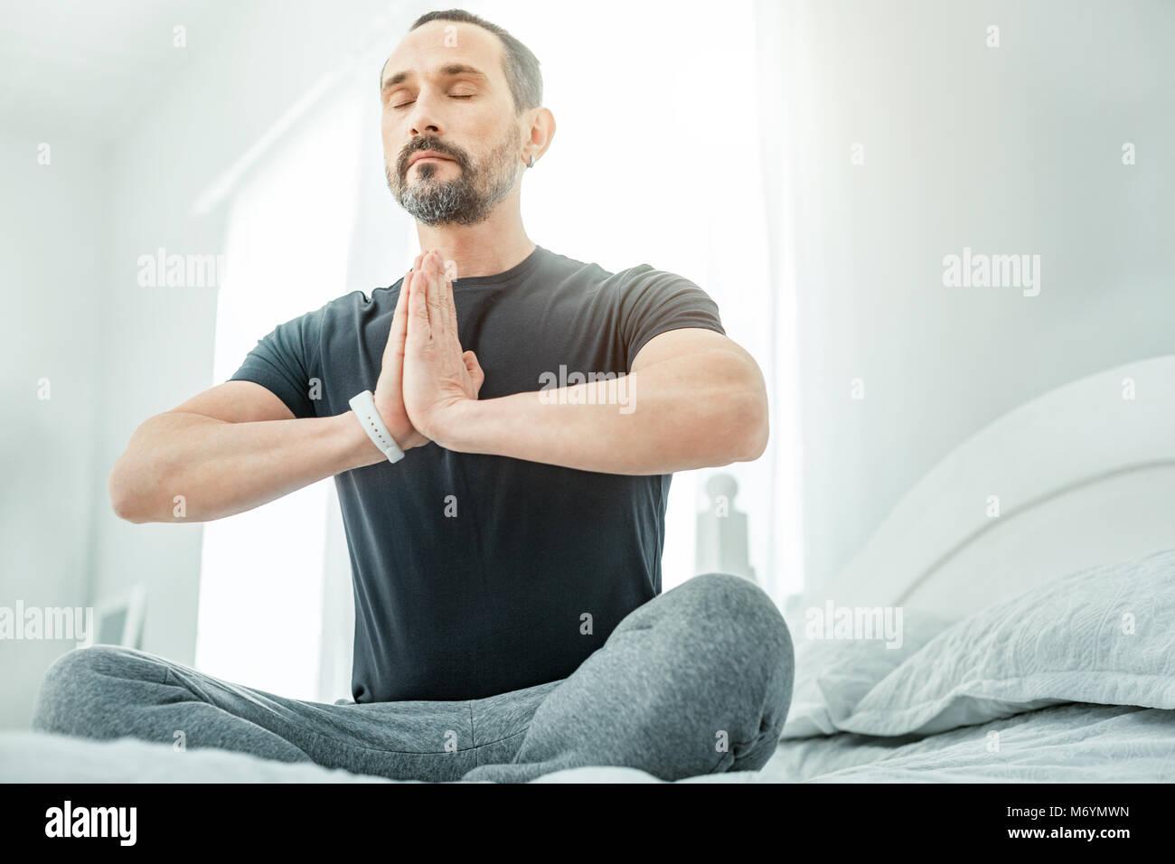 Calm healthy man sitting closing his eyes. - Stock Image