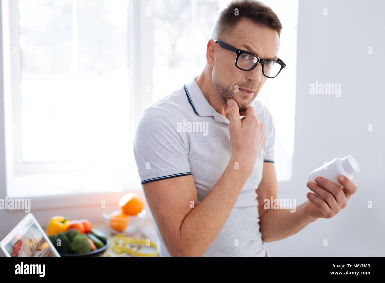 Pensive thoughtful man studying biohacking drug - Stock Image