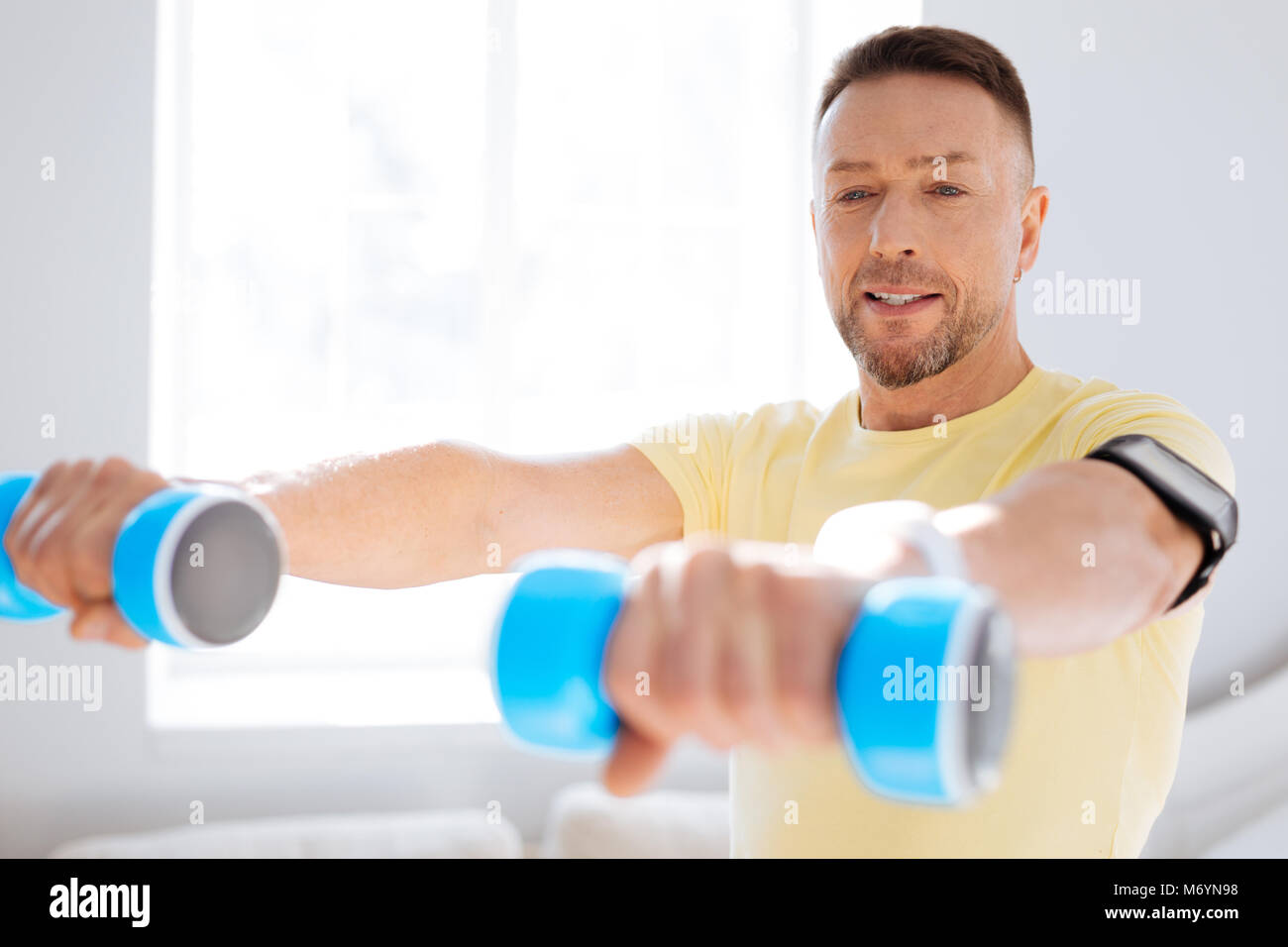 Earnest nice man working out with dumbbells - Stock Image