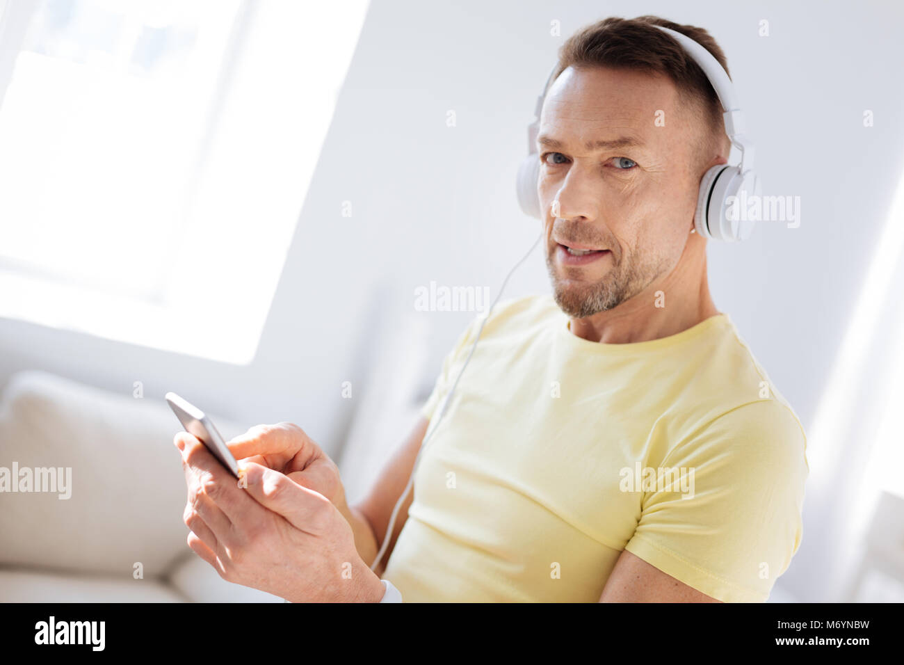 Inspired thoughtful man opting music - Stock Image