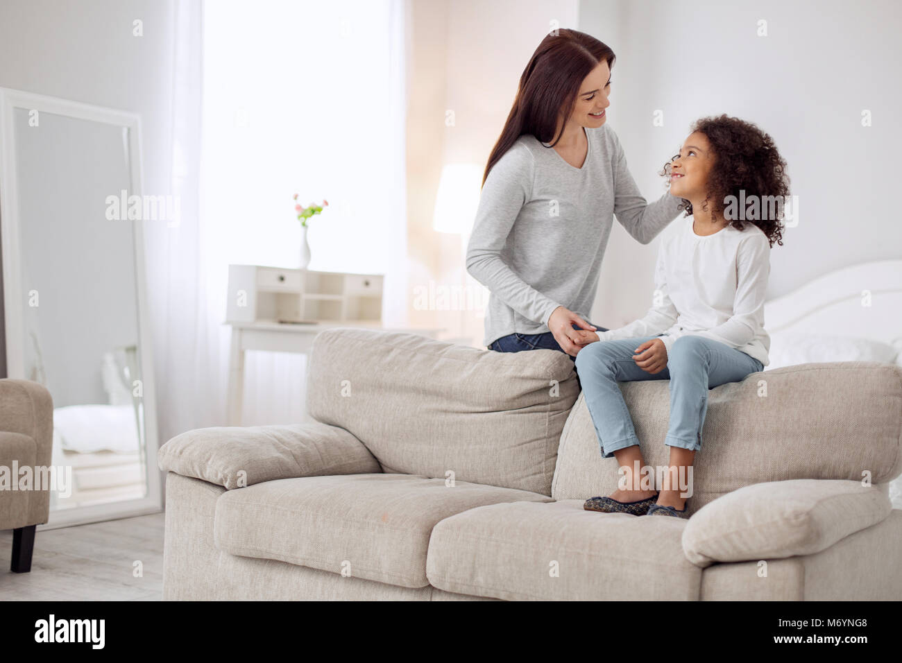 Happy mother caressing her daughter - Stock Image