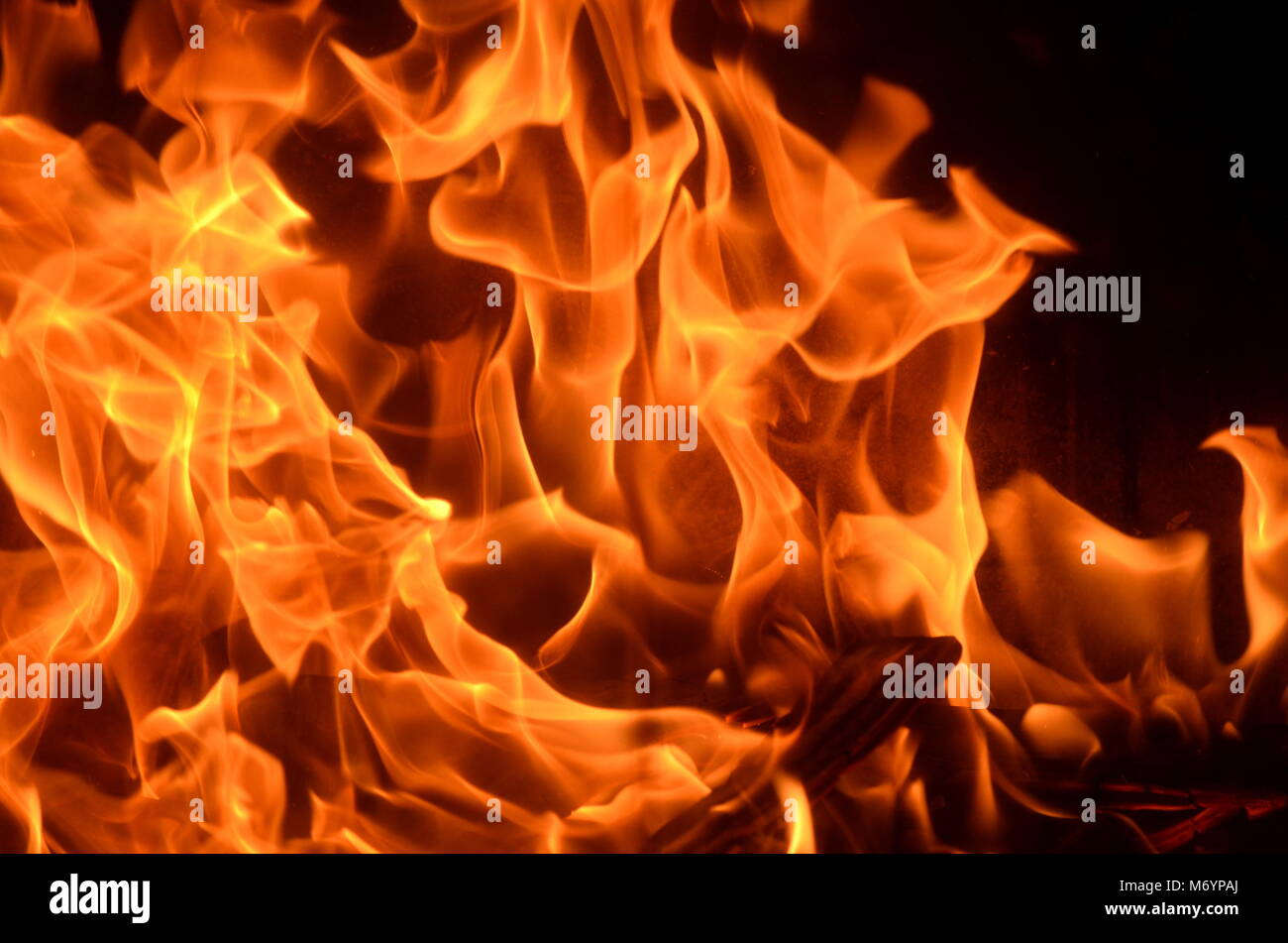 Close up of burning fire with blazing red, orange and yellow flames background. Fire hazard, fire safety, arson, - Stock Image