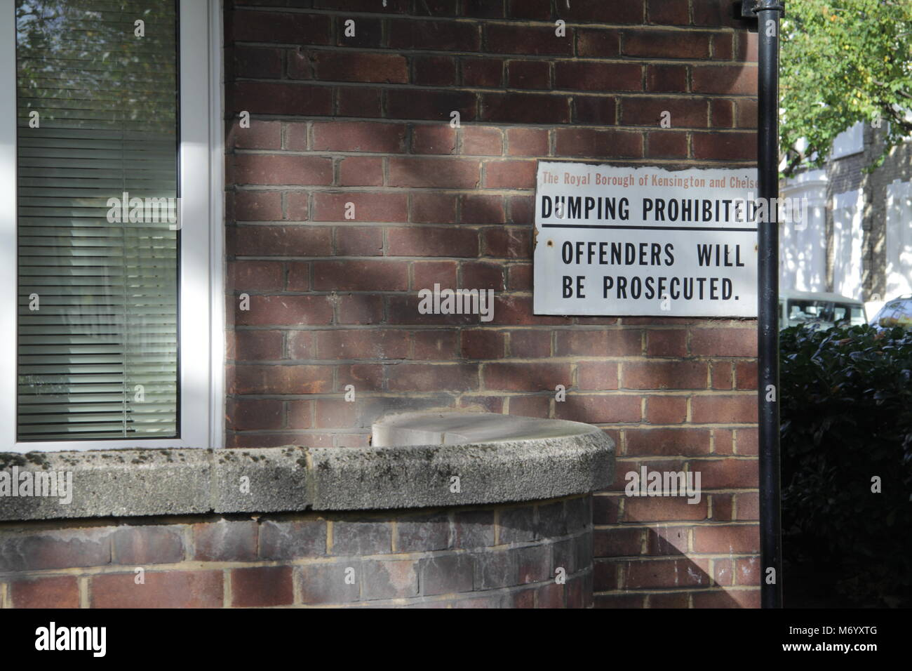 Dumping Prohibited Sign on brickwork brick wall in West London - Stock Image