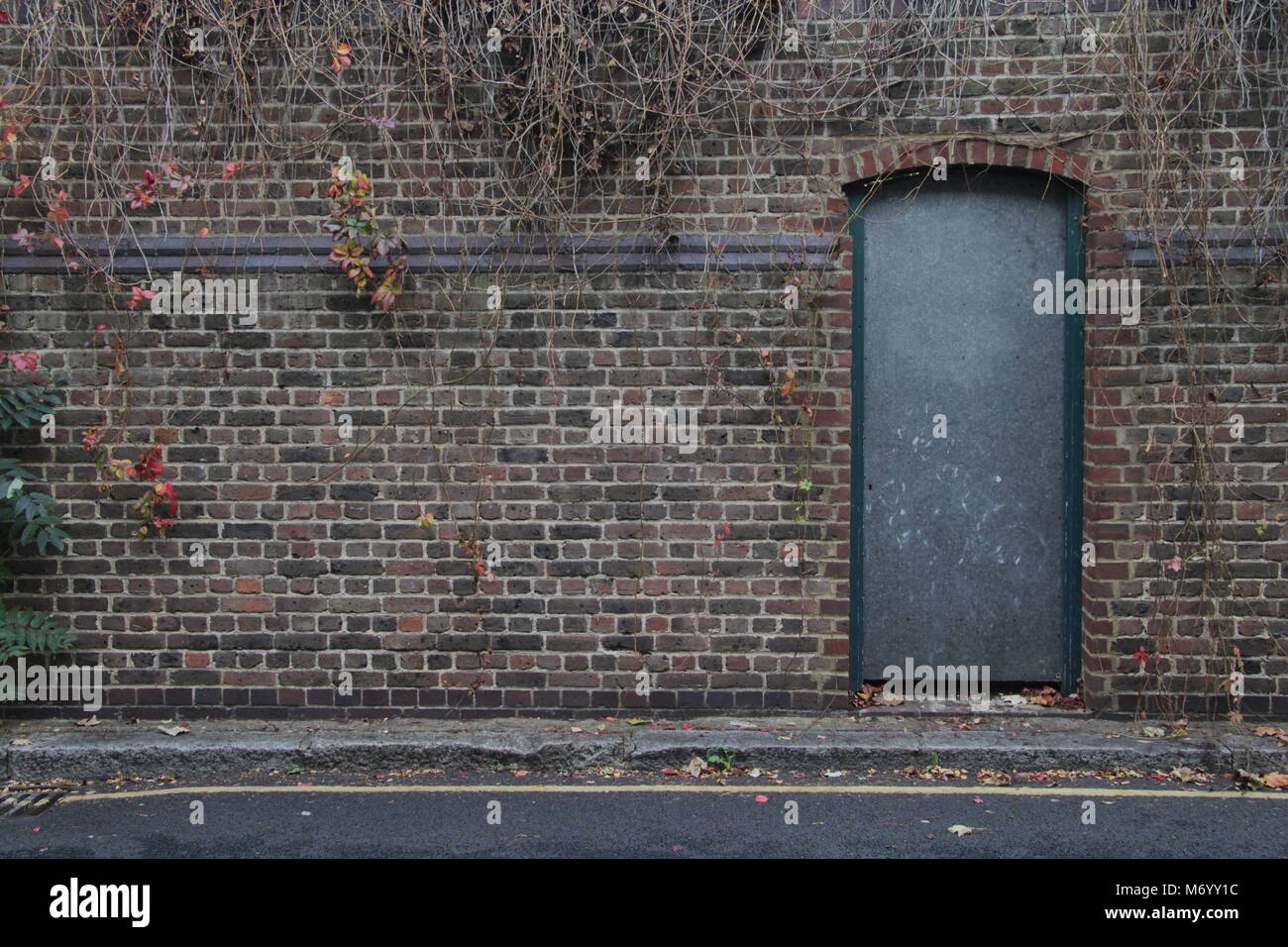 Closed Metal Door on a brickwork brick wall in west London - Stock Image