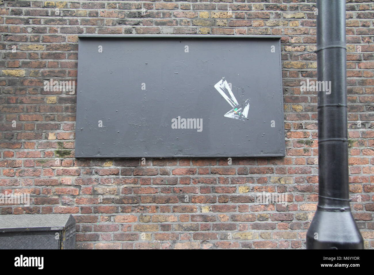 Sign on Brickwork wall in west London, Arrow has been stencilled onto the blank noticeboard - Stock Image