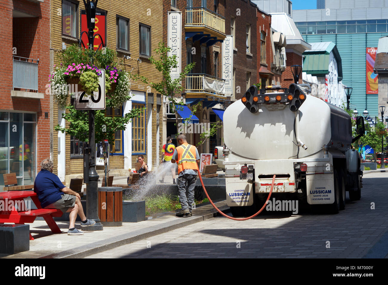 Montreal city employee watering trees and plants on the street. - Stock Image