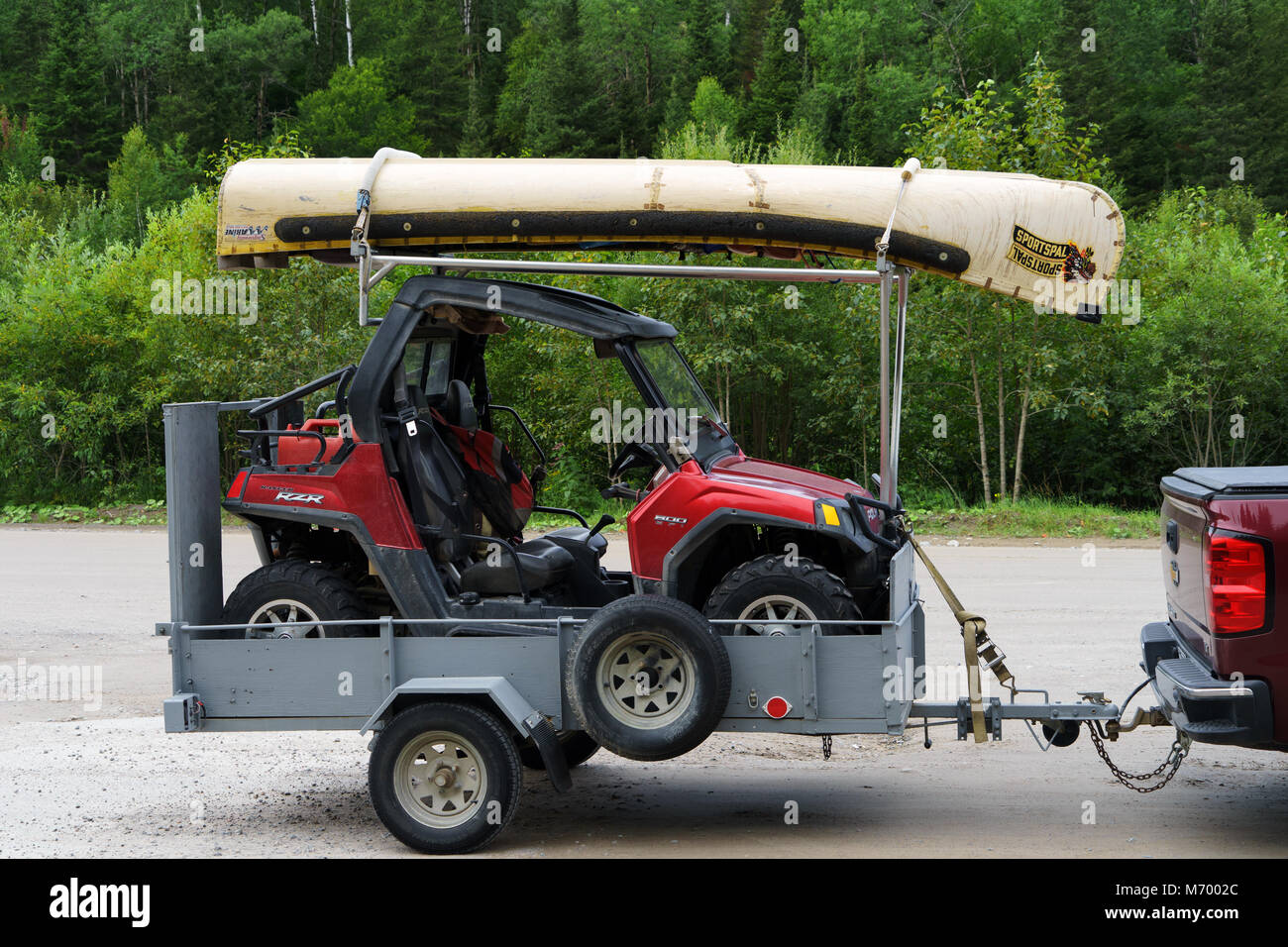 Small offroad vehicle and canoe on a trailer, Canada. - Stock Image