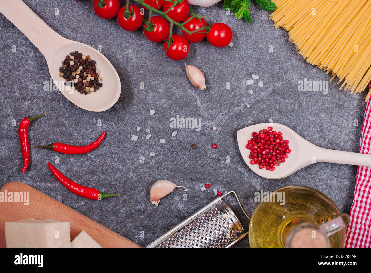 traditionally the Italian food background, with spaghetti, parmesan, olive oil, garlic, peppercorns, rosemary, cherry - Stock Image