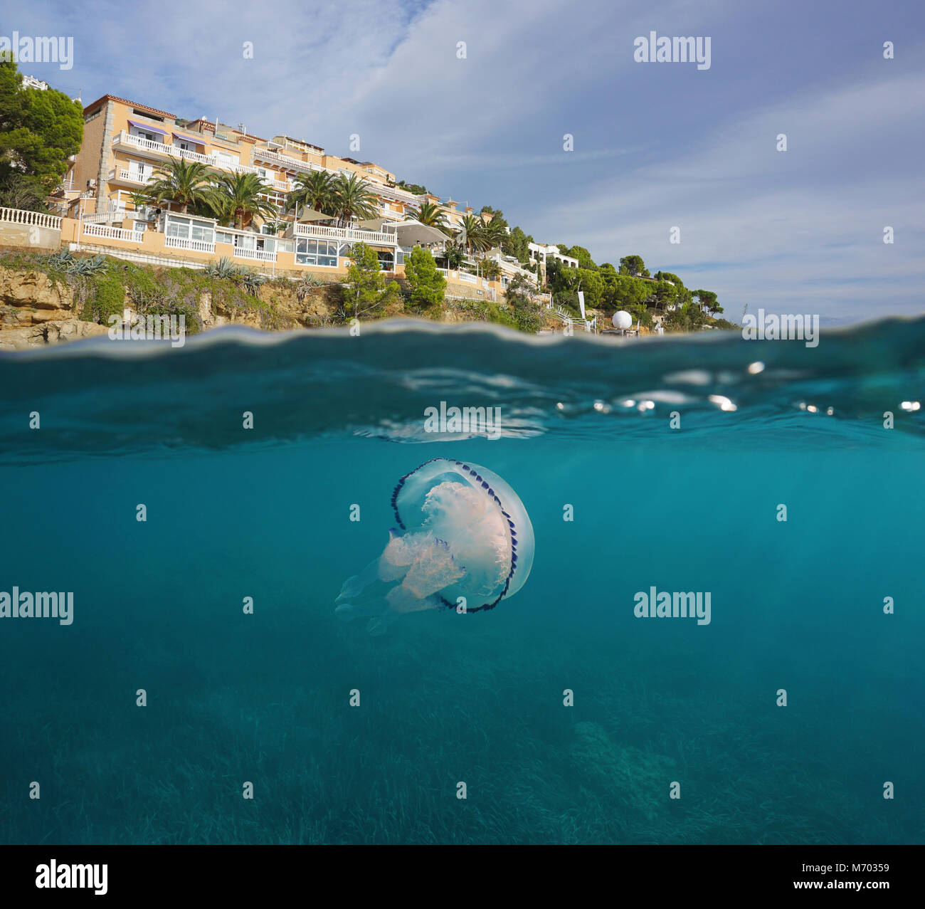 Hotel on the coast of the Mediterranean sea with a jellyfish underwater, split view above and below water surface, - Stock Image