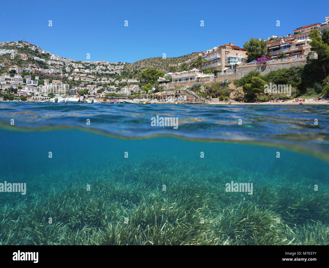 Seaside town in Spain on the Costa Brava and seagrass meadow underwater, split view above and below water surface, - Stock Image