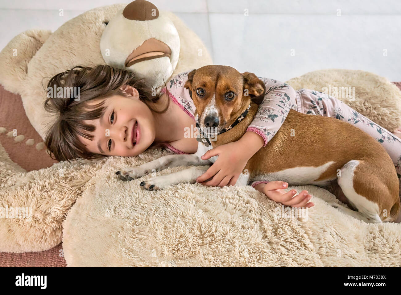 Six year old girl and her doggie laying on a giant bear Stock Photo