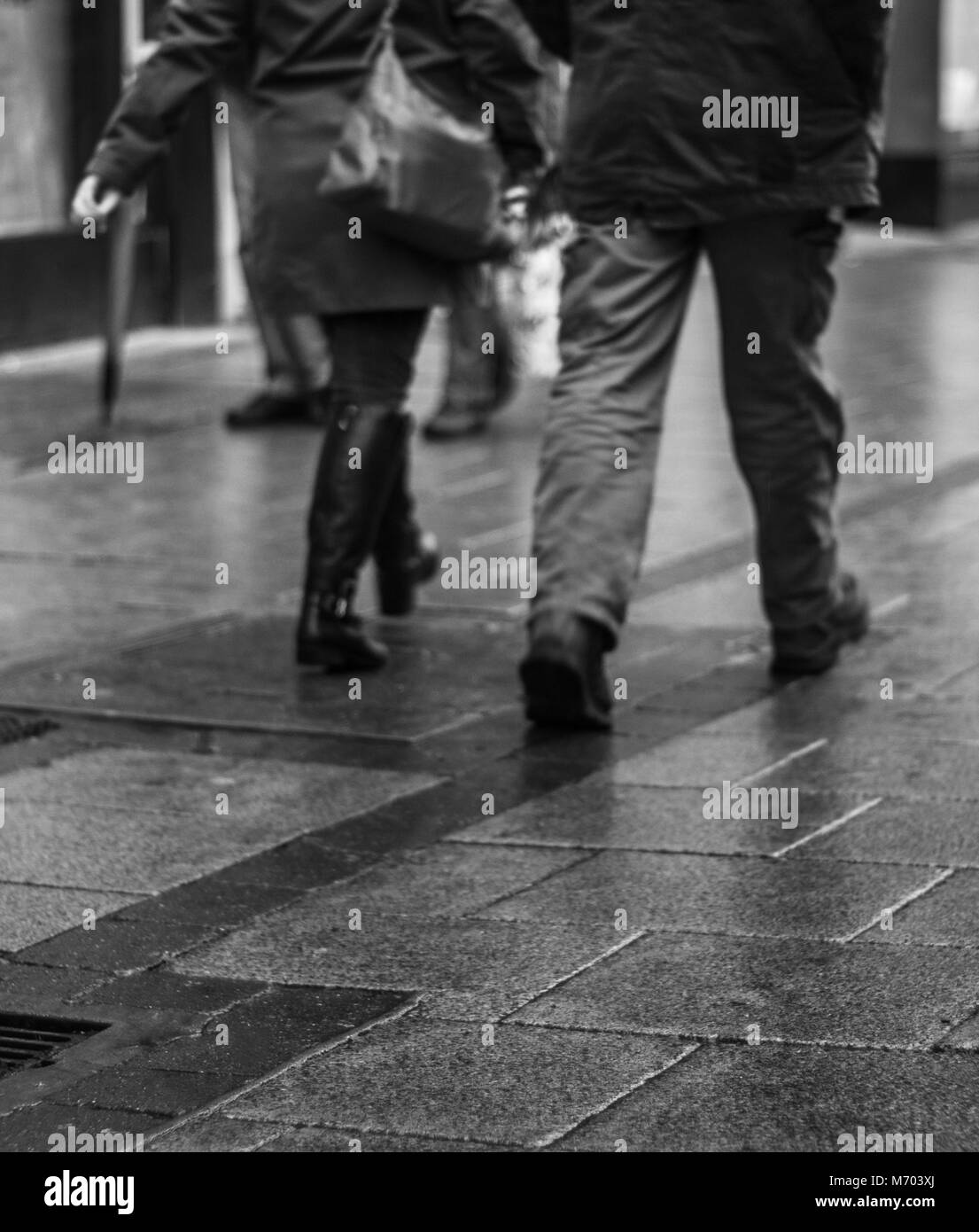 Legs of two people walking down a rainy Street whilst shipping - Stock Image