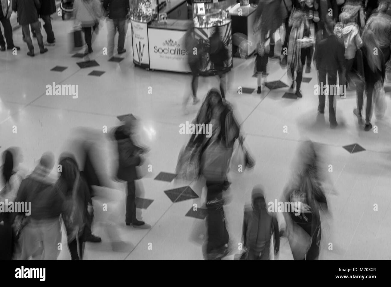 People walking through a shopping mall, taken with a slow exposure to blur the people - Stock Image