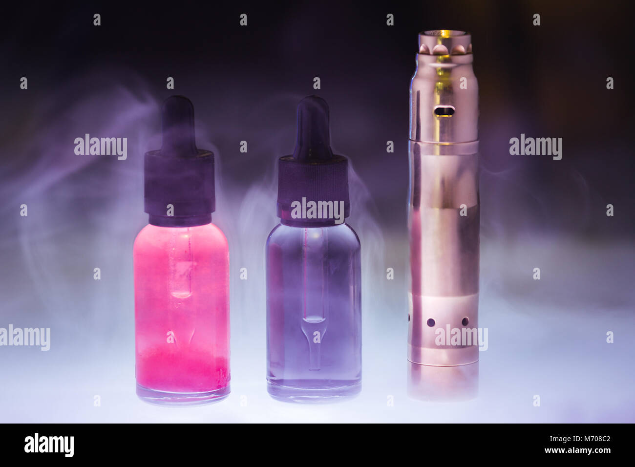 E-cigarette with two e-liquid in the white smoke on a dark background. E-juice from vape. Alternative to smoking - Stock Image