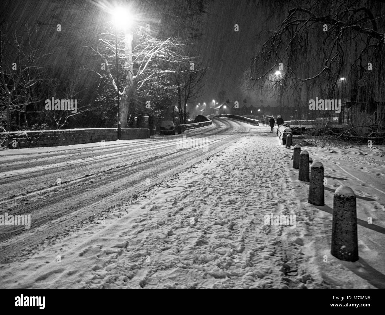 Late evening snow fall in Otley showing Bridge street and road bridge spanning the River Wharfe - Stock Image