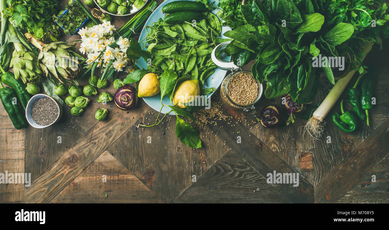 Spring healthy vegan food cooking ingredients, wooden background, wide composition - Stock Image