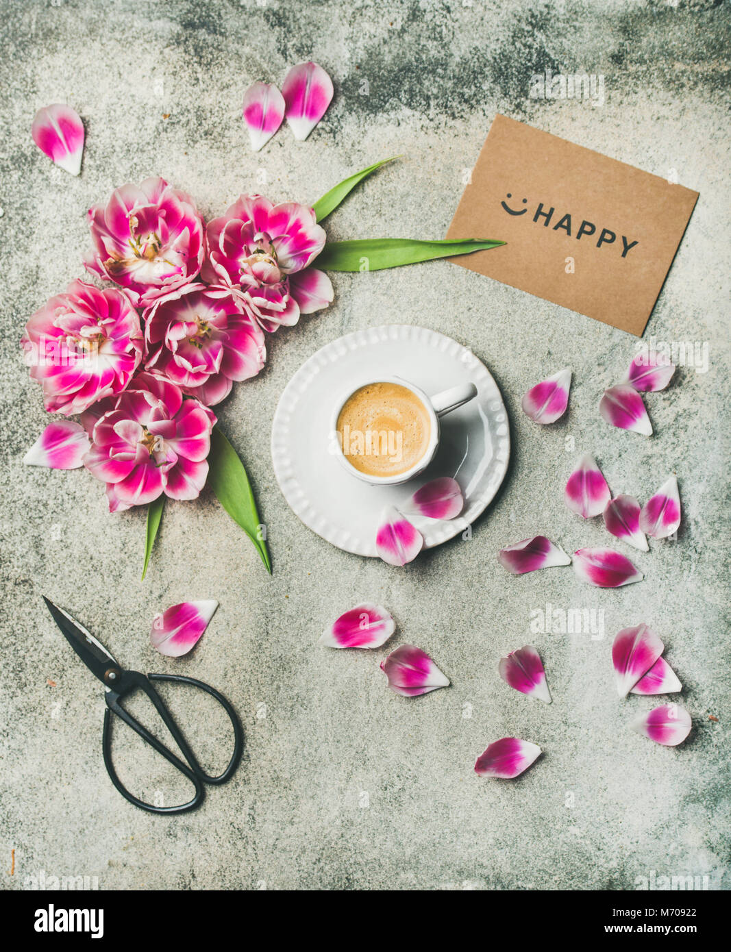 Cup of coffee surrounded with pink tulip flowers - Stock Image
