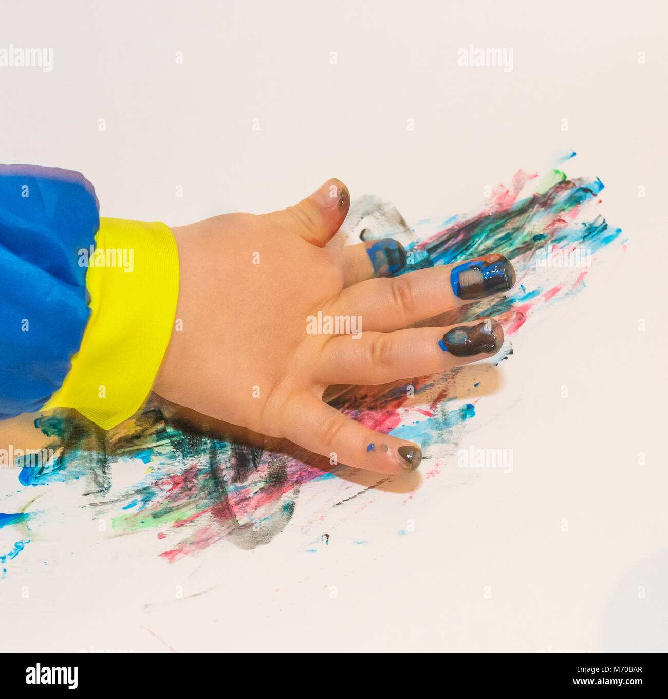 Child hand painted in colorful paits. Education, school, creativity and painting concept. Soft focus an blurry - Stock Image