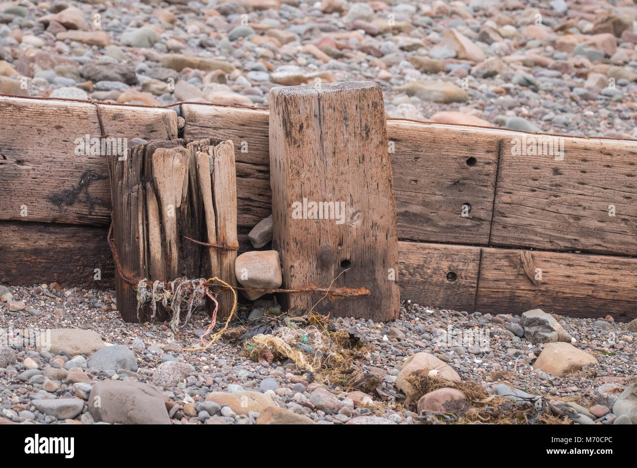 View showing part of a groyne on a beach with rocks and sand round about. Stock Photo