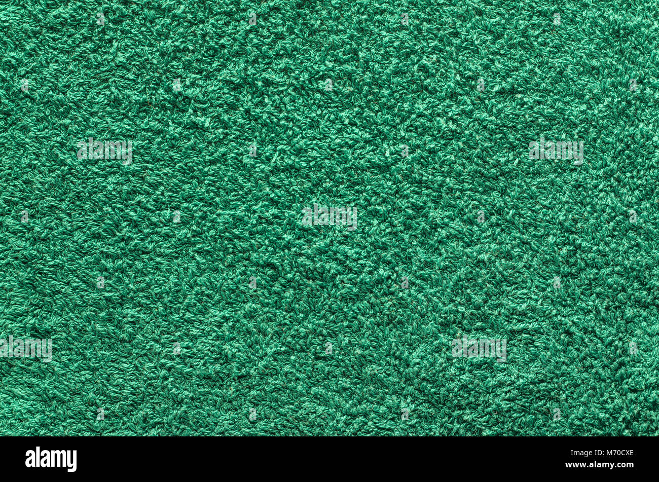 Abstract background of shaggy green carpet pile. Cloth texture with long fibers - Stock Image