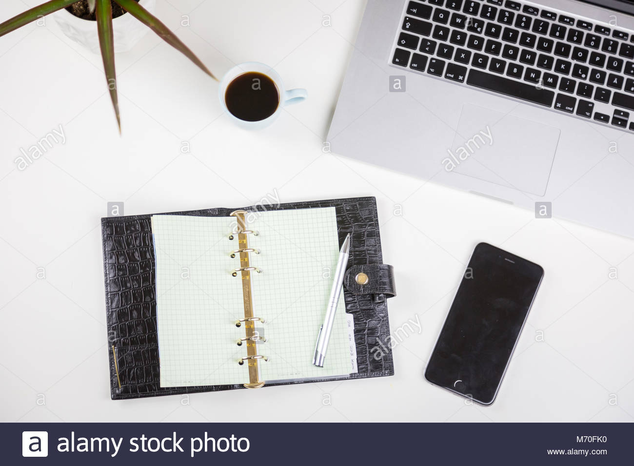 Open diary alongside a potted plant and mobile - Stock Image