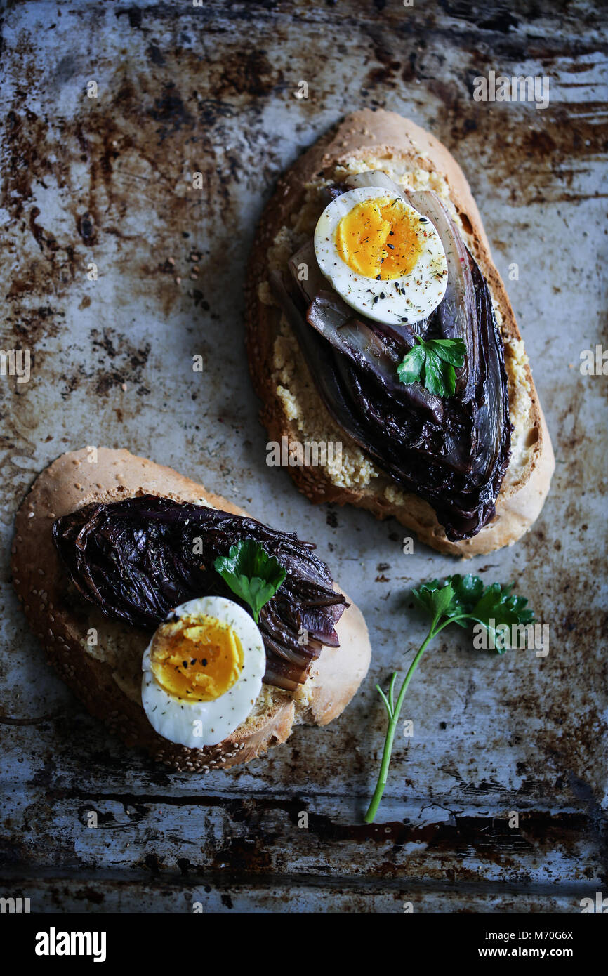 Braised red chicory crostini with hummus, boiled egg and spices - Stock Image