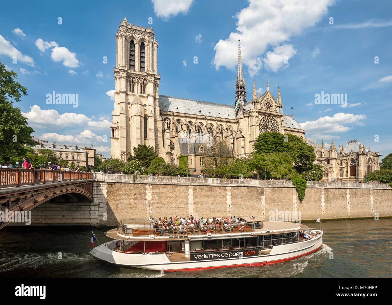 PARIS, FRANCE:  Bateaux Mouche on the River Seine passing Notre-Dame Cathedral on the Ile de la Cite - Stock Image