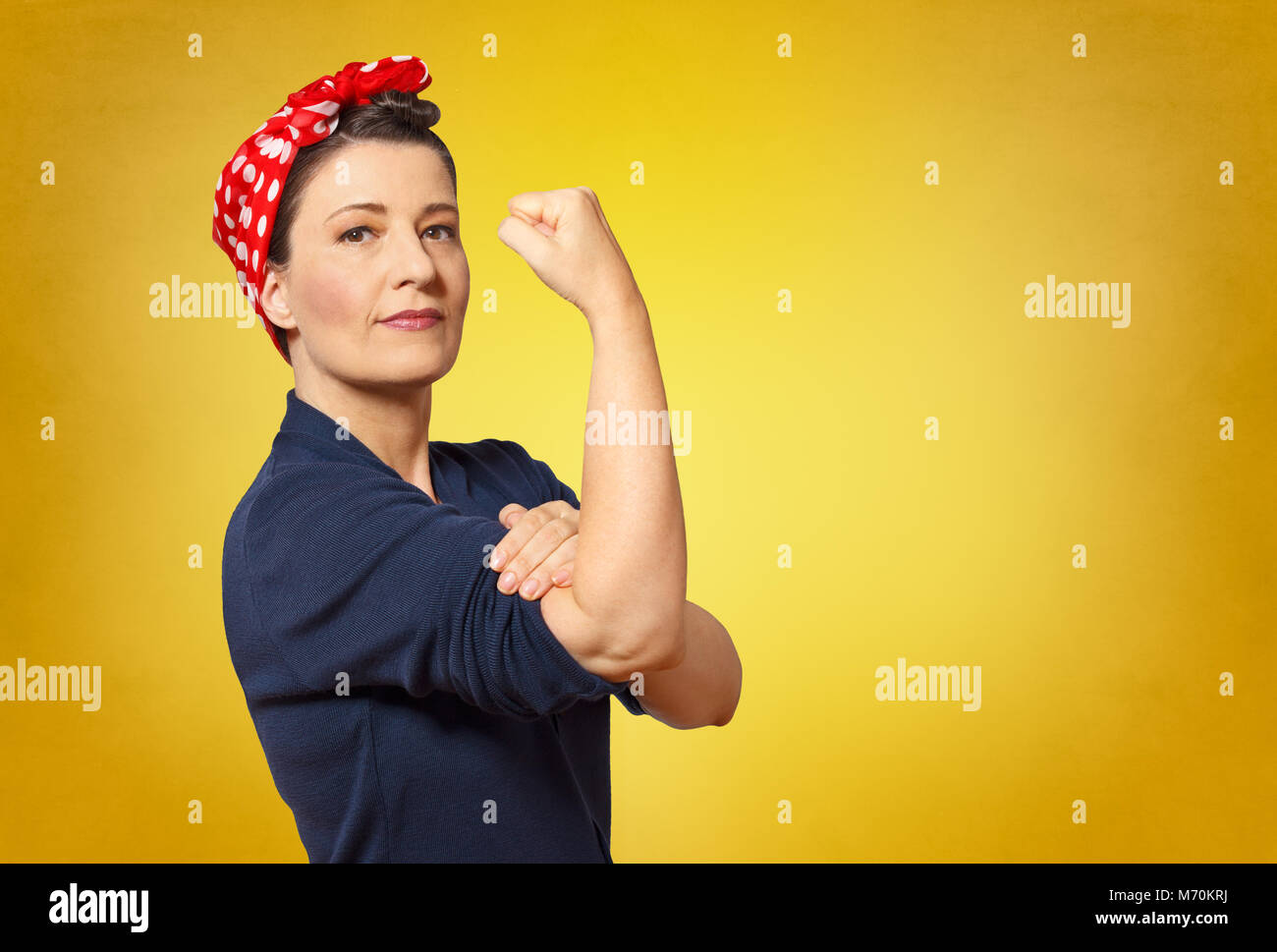 Self-confident middle aged woman with a clenched fist rolling up her sleeve, text space, tribute to american icon - Stock Image