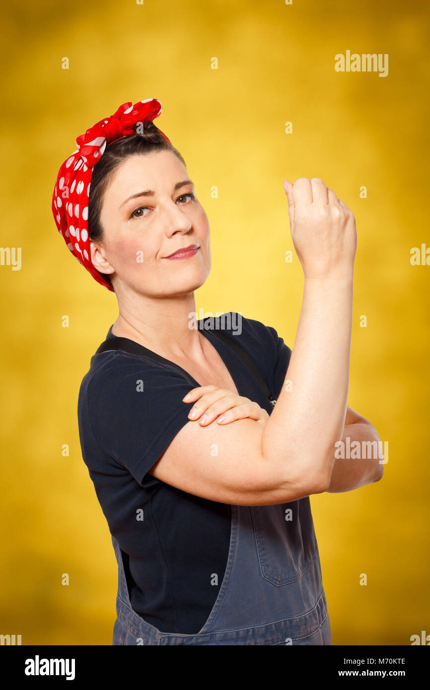 Self-confident middle aged woman with dungarees rolling up her sleeve, text space, tribute to american worker icon - Stock Image