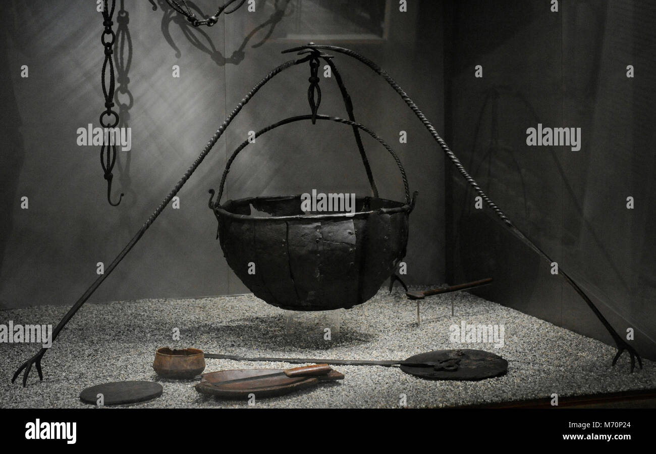 Group of Viking utensils. Chain for cauldron and iron cauldron with tripod. In the bottom, wooden bowl, bowl and - Stock Image