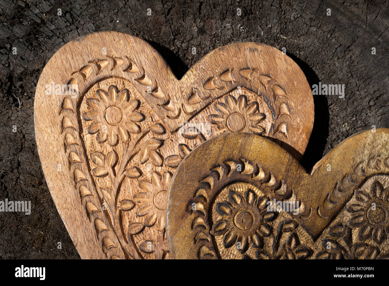 Top half of two wooden hearts, one slightly over the other, both hearts have flower and other patterns craved in - Stock Image