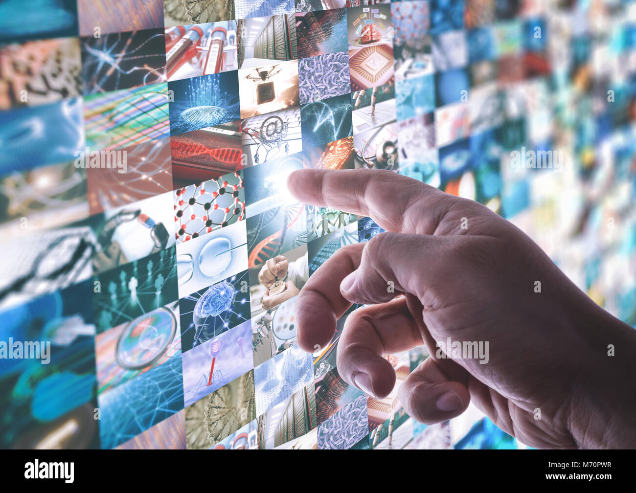 The hand touches the touchscreen led panel with various images about technology and science. - Stock Image