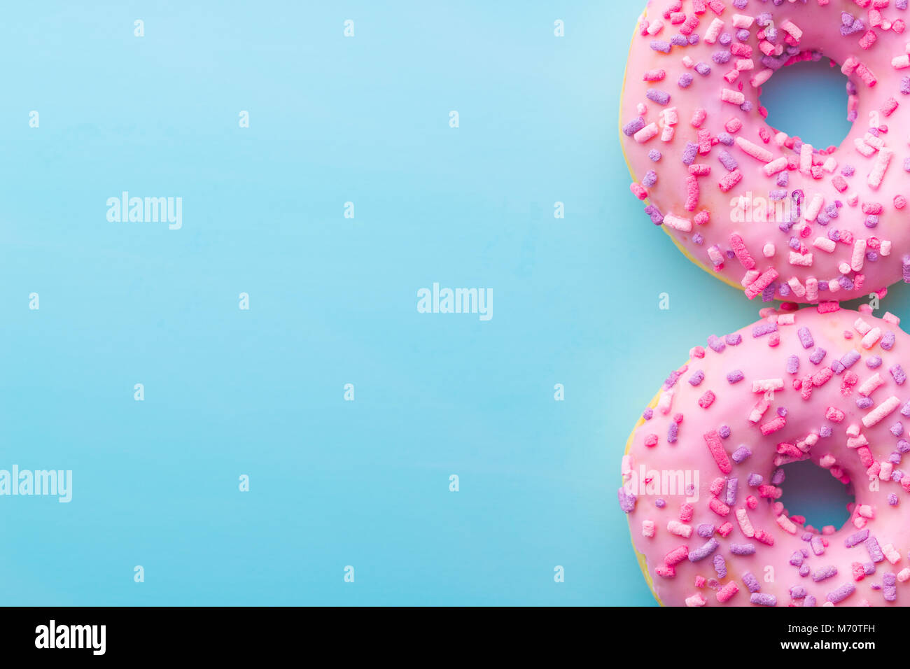 Two pink donuts on blue background. - Stock Image