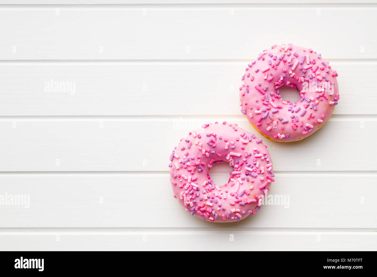 Two pink donuts on white table. - Stock Image