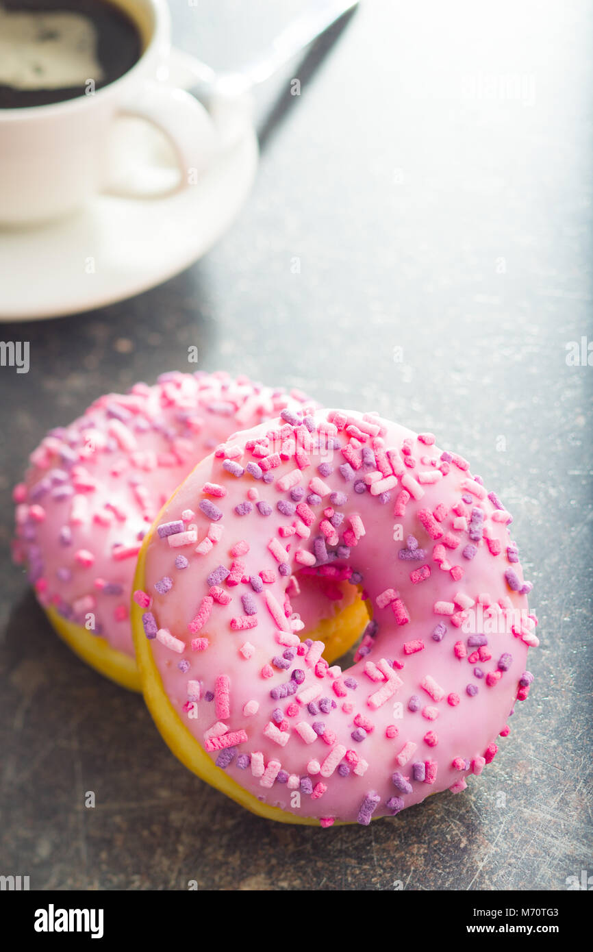 Two pink donuts on old kitchen table. - Stock Image