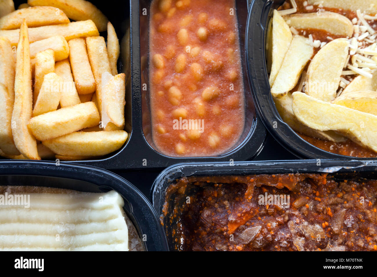 Selection of frozen, processed, ready made foods, consisting of potato chips, mince, lasagna in black, plastic containers - Stock Image