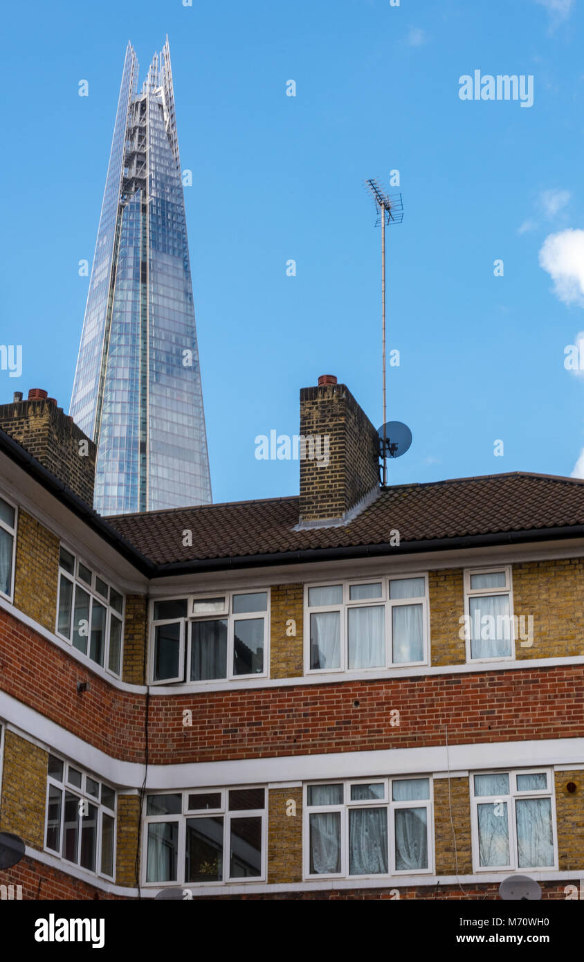 a stark contrast between the modern and contemporary shard office building in central london and some local authority Stock Photo