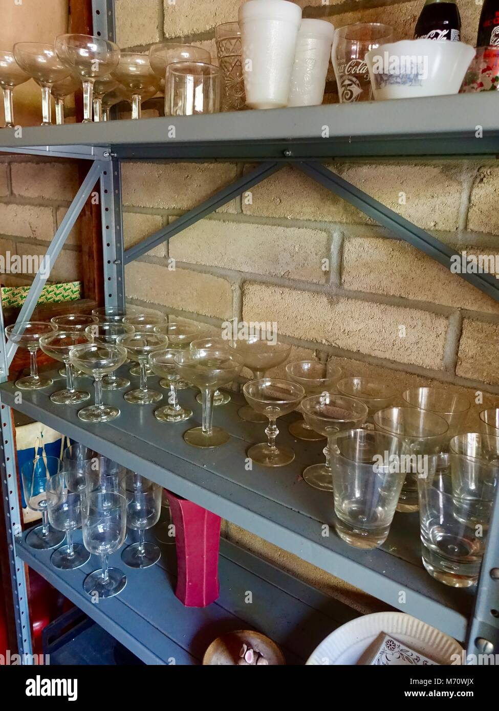 Glassware stored on shelves in garage, ready for garage sale. - Stock Image