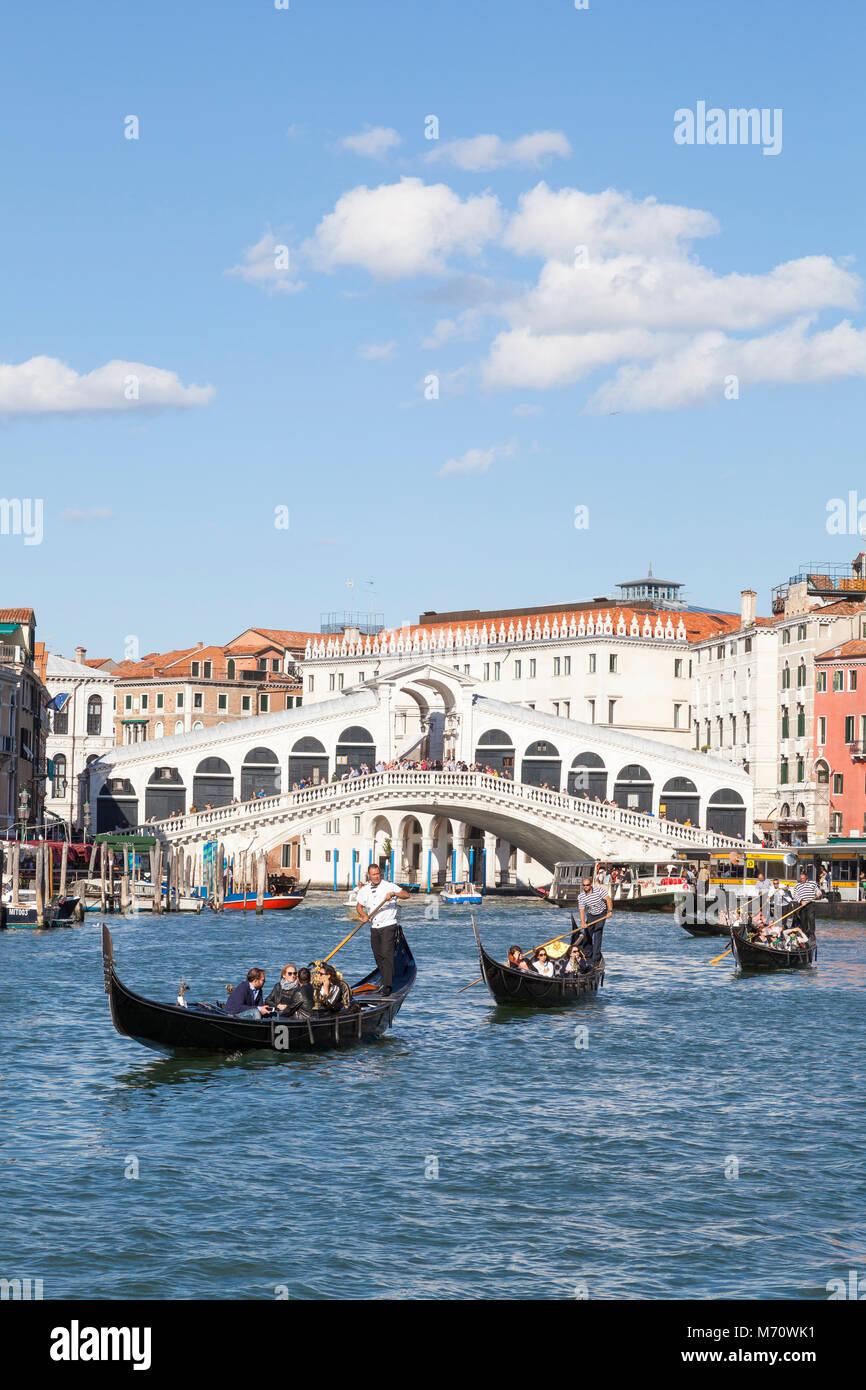 Line of gondolas with tourists on the Grand Canal, Rialto Bridge, Venice,  Veneto, italy enjoying a sightseeing - Stock Image