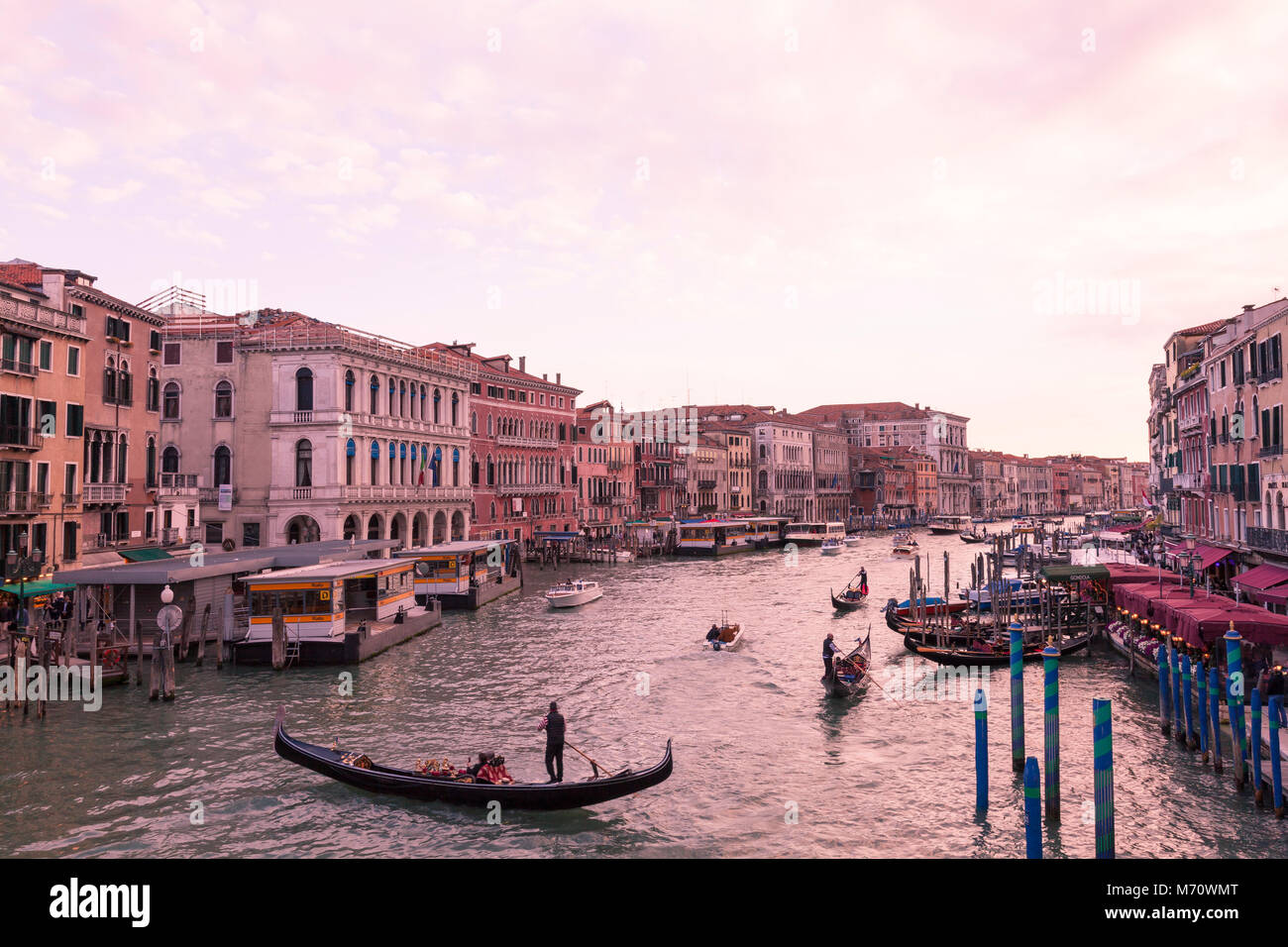 Colorful pink sunset  at dusk over the Grand Canal, Venice, Italy as viewed from Rialto Bridge over Riva del Vin Stock Photo