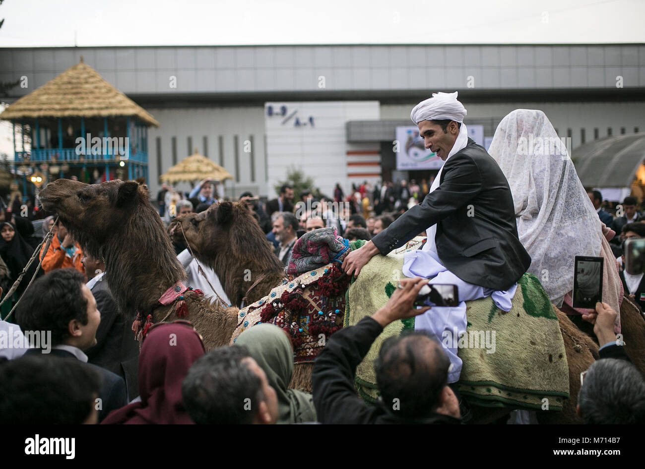 Tehran, Iran. 7th Mar, 2018. Iranian rural bride and groom wearing local costumes ride a camel at a symbolic wedding - Stock Image