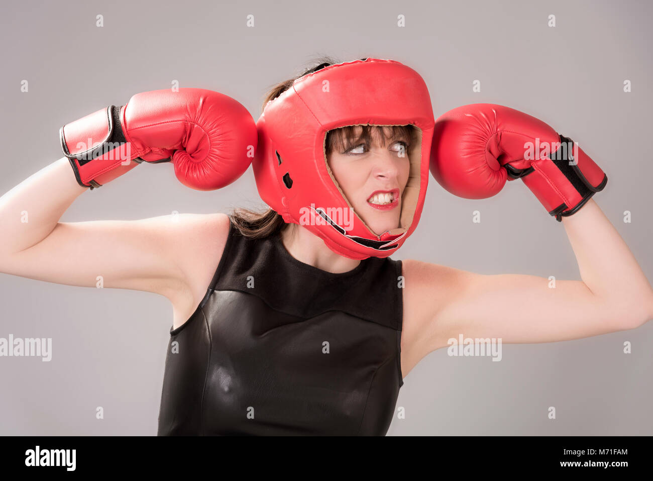 Woman boxer with an facial expression wearing a red headguard and red boxing gloves, Circa 2018 - Stock Image