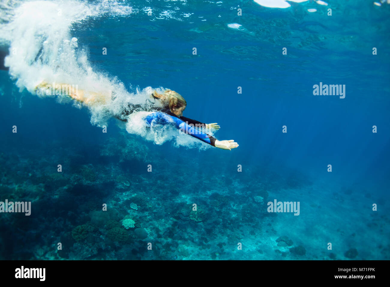 Happy family - active teenage girl jump and dive underwater in tropical coral reef pool. Travel lifestyle, water - Stock Image