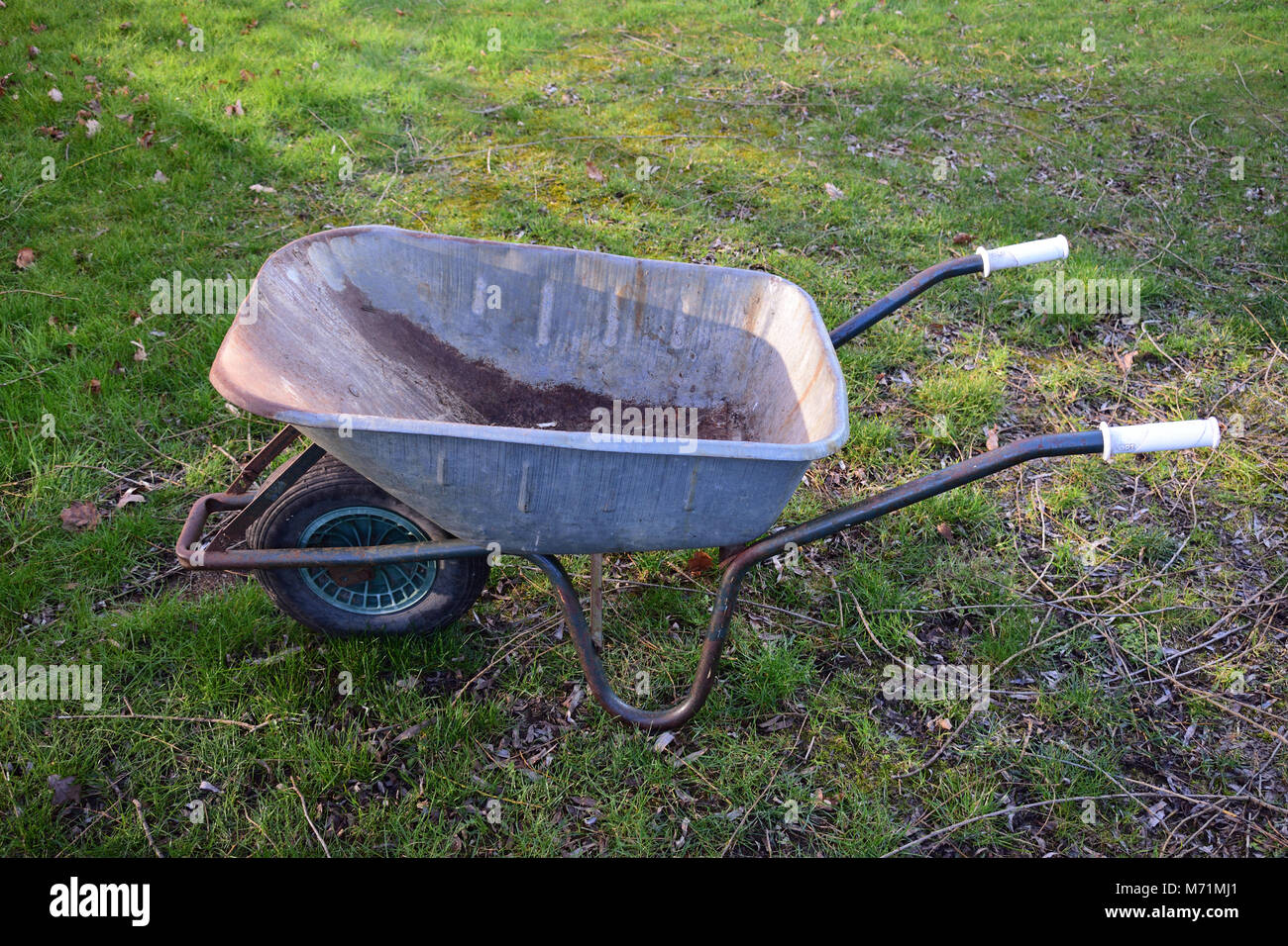 Used stainless steel wheelbarrow in the grass - Stock Image