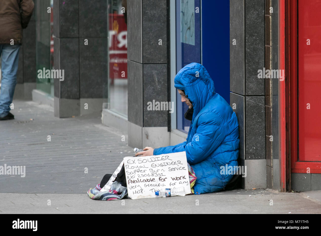 homeless homelessness beg beggar tramp swep rough sleeper sleeping cold street poor hungry person bag lone alone - Stock Image
